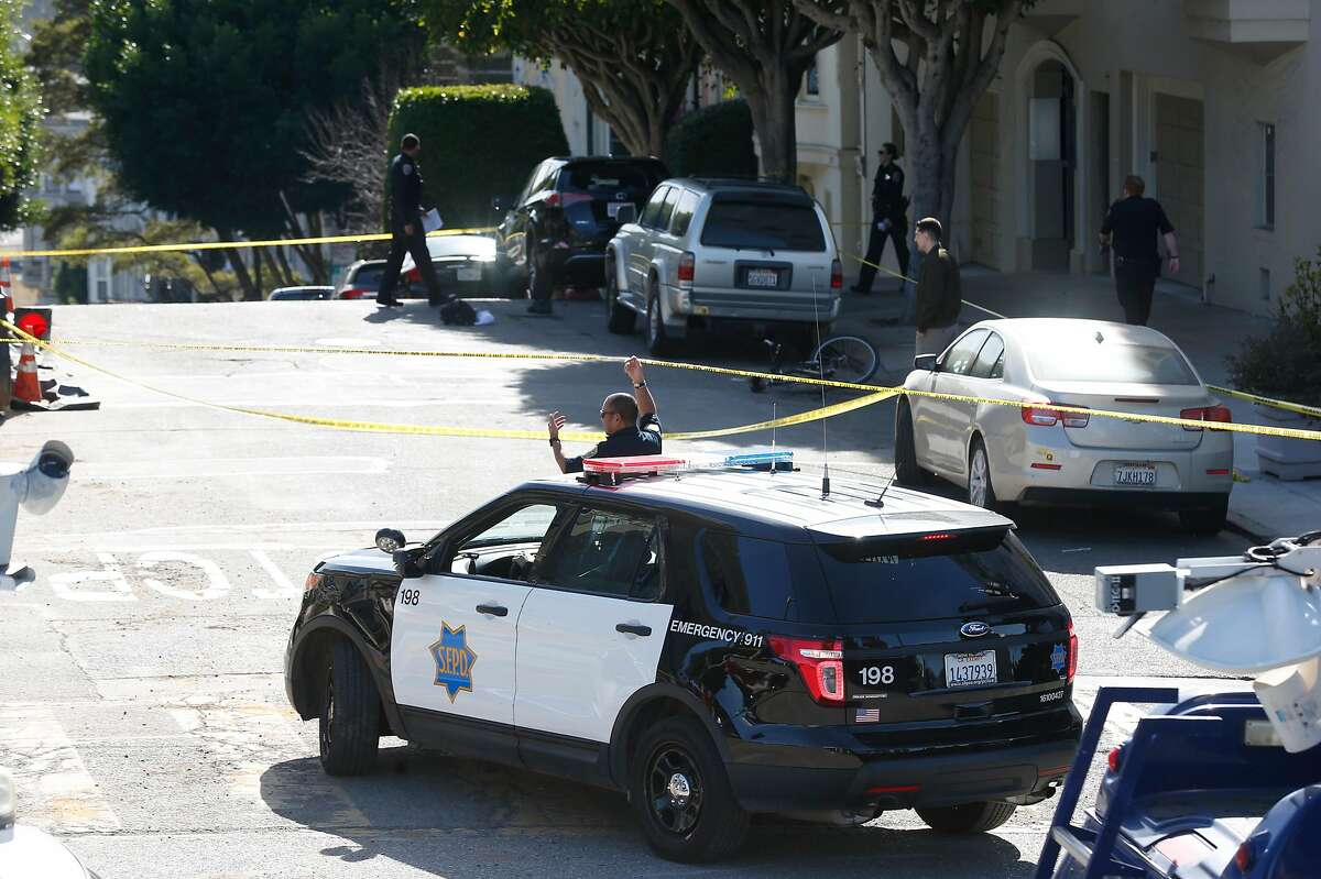 Police officers protect evidence at Pierce and Hayes streets across from Alamo Square after an officer, working an auto burglary detail, was struck and injured by a vehicle driven by one of the suspects in San Francisco, Calif. on Thursday, Feb. 1, 2018.