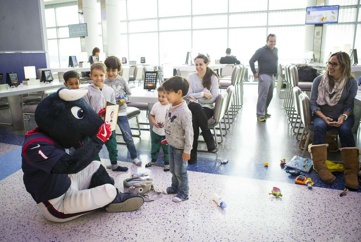 Houston Texans mascot Toro stops to surprise a group of young travelers on his way to visit a United flight to Chicago O'Hare with players Kareem Jackson (25), DJ Reader (98) and Benardrick McKinney (55) at George Bush Intercontinental Airport, Thursday, Feb. 1, 2018, in Houston. ( Mark Mulligan / Houston Chronicle )