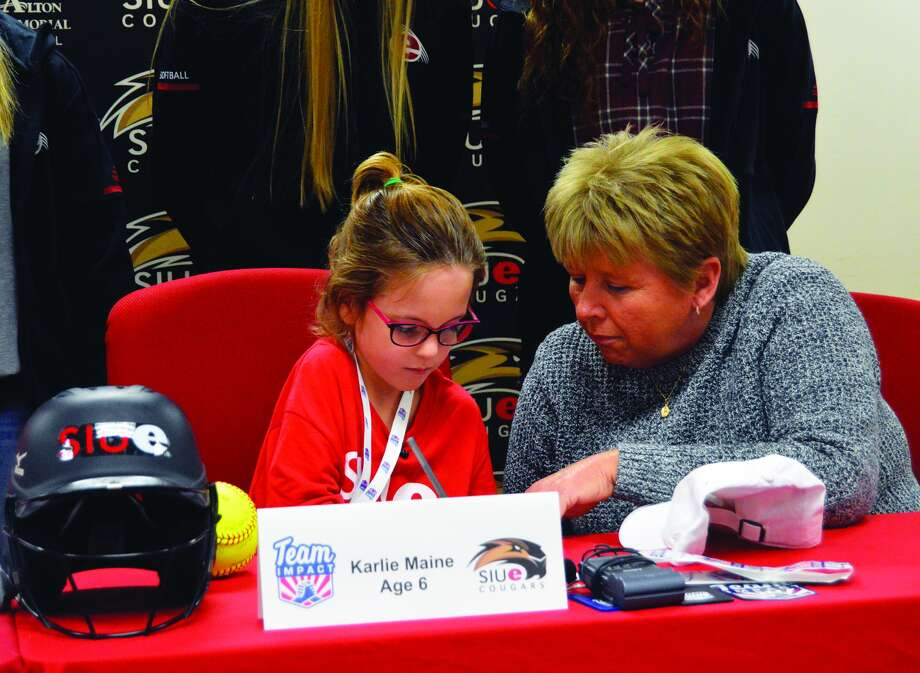 Karlie Maine, a 6-year-old from Alhambra, signs a national letter of intent to join the SIUE softball program on Thursday. Coach Sandy Montgomery is seated with Maine.