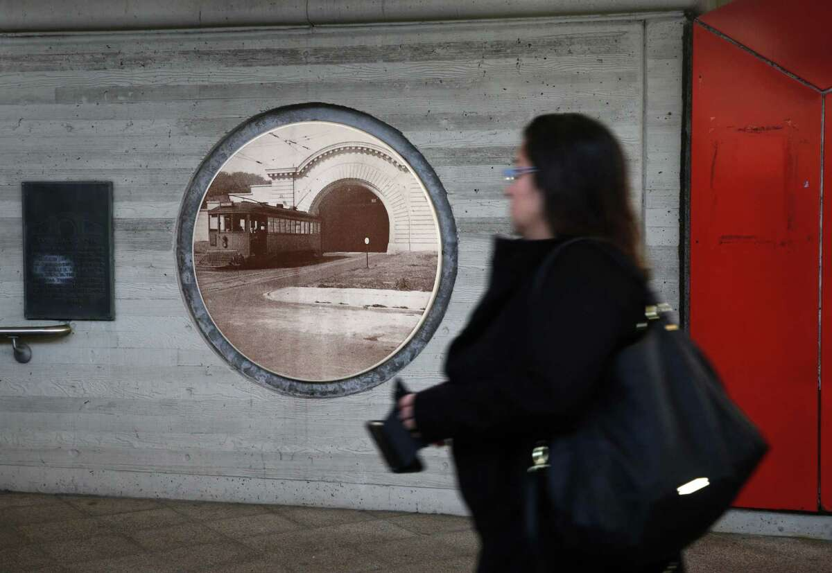 A commuter walks past a historic photograph of the Twin Peaks Tunnel displayed at West Portal Station.