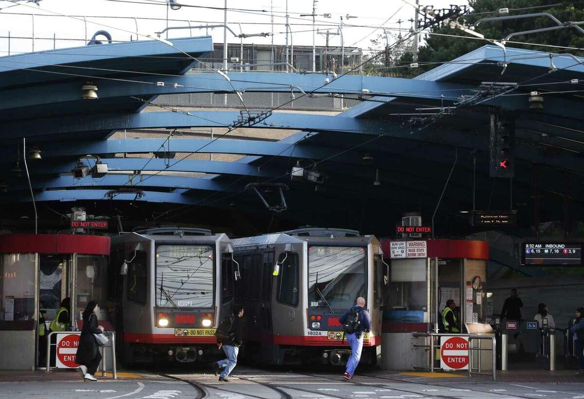 Muni Metro trains arrive and depart West Portal Station.