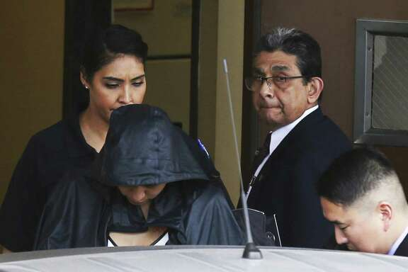 Hidden under security and a jacket, Denise Cantu (front left), the Harlingen woman who prosecutors allege Carlos Uresti carried on a sexual relationship with and then exploited by convincing her to invest in a startup oil field company, is returning to the witness stand Friday in the state senator's criminal fraud trial on Thursday, Feb. 1, 2018.