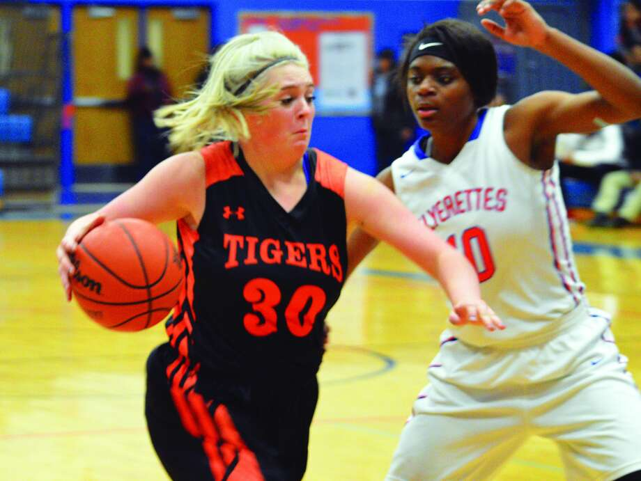 Edwardsville junior Morgan Hulme, left, drives to the basket during the third quarter of Thursday's Southwestern Conference game at East St. Louis.