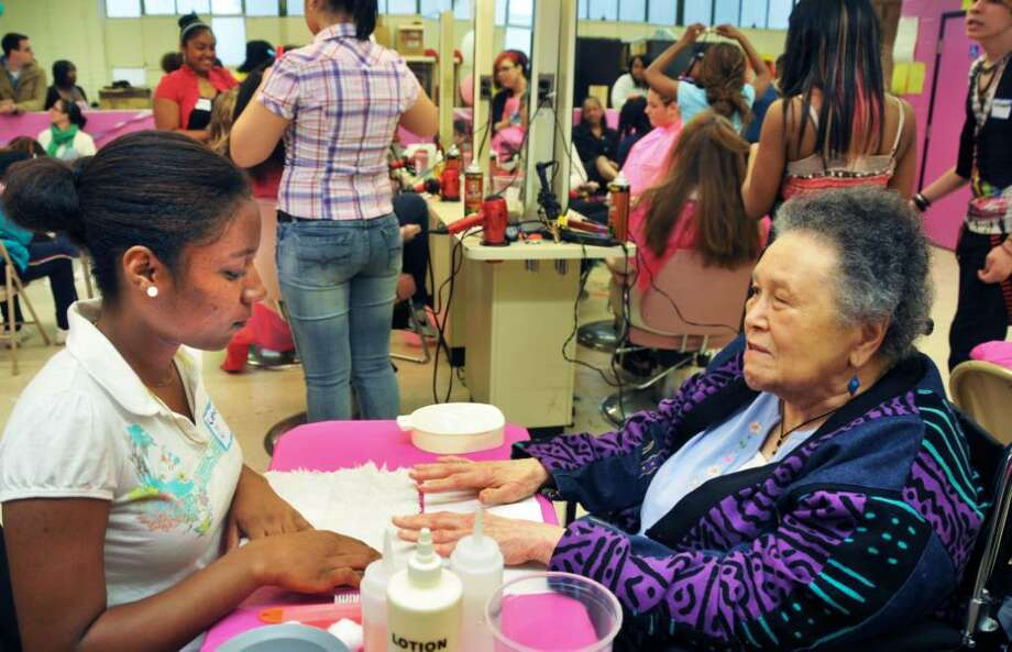 Margaret Cunningham, 91, of Schenectady, gets a manicure from Albany High cosmetology student Latasia George, 17,  as students and faculty at Abrookin Vocational-Technical Center in Albany host a Mother's Day on May 8.  (John Carl D'Annibale / Times Union) Photo: John Carl D'Annibale / 00008647A