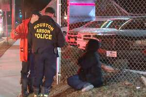 Houston Fire Department officials talk to a woman who escaped a fire at a home on Crosstimbers at Roswell, Feb. 2, 2018.