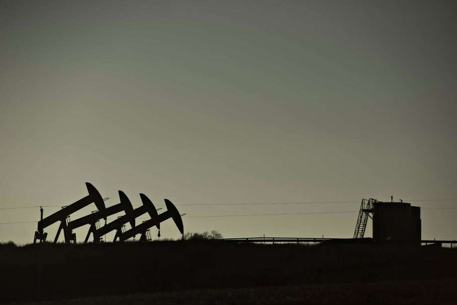 28fba59cefecff Four pumpjacks are silhouetted as they operate at the site of an oil well  in North