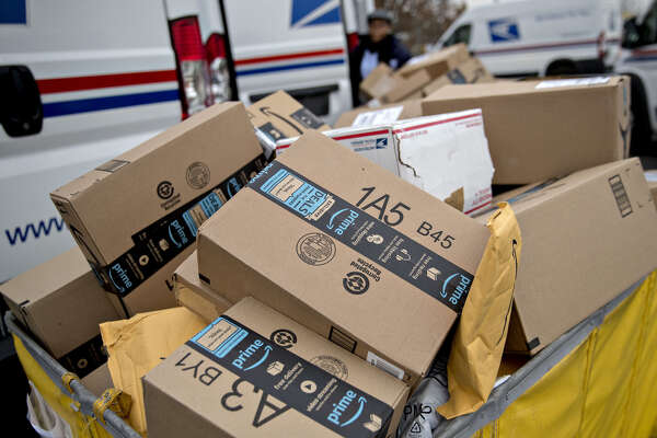 Amazon.com packages sit in a bin before being placed on a U.S. Postal Service delivery vehicle in Washington on Dec. 12, 2017.