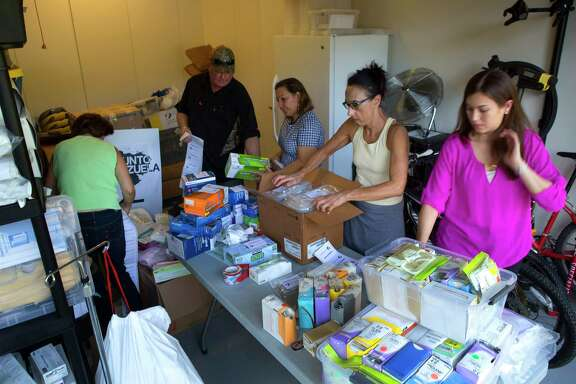 Volunteers fill the garage of Maria Cristina Manrique de Henning to pack up medical supplies and medicine to be sent to Venezuela as part of Operacion Saludos a Venezuela, Tuesday, Aug. 2, 2016, in Houston.