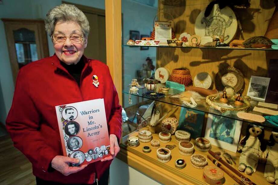 Midland resident Quita Shier poses for a photo with a copy of her book, 'Warriors in Mr. Lincoln's Army,' which focuses on the soldiers in an all-Native American company during the Civil War. (Katy Kildee/kkildee@mdn.net)