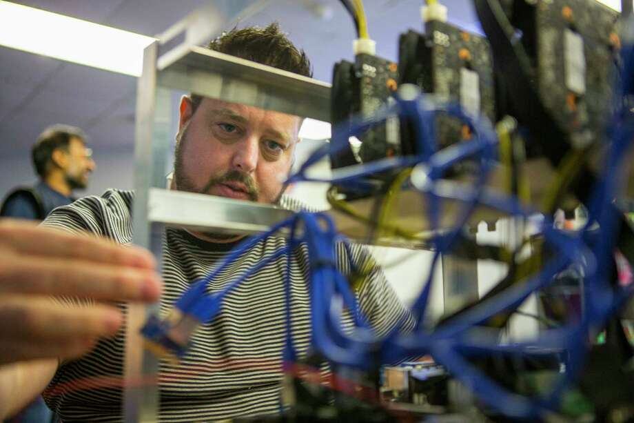 Kyle Walton works on a cryptocurrency mining rig inside the Snapstream offices. The rigs use high-powered video cards. Photo: Mark Mulligan, Houston Chronicle / © 2018 Houston Chronicle