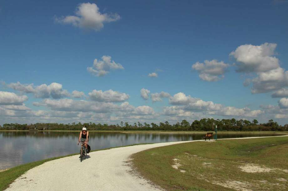 A cyclist tours the 1.75-mile track around Sunset Lake at Babcock Ranch in Southwest Florida. Photo: Photo By Selina Kok For The Washington Post. / The Washington Post