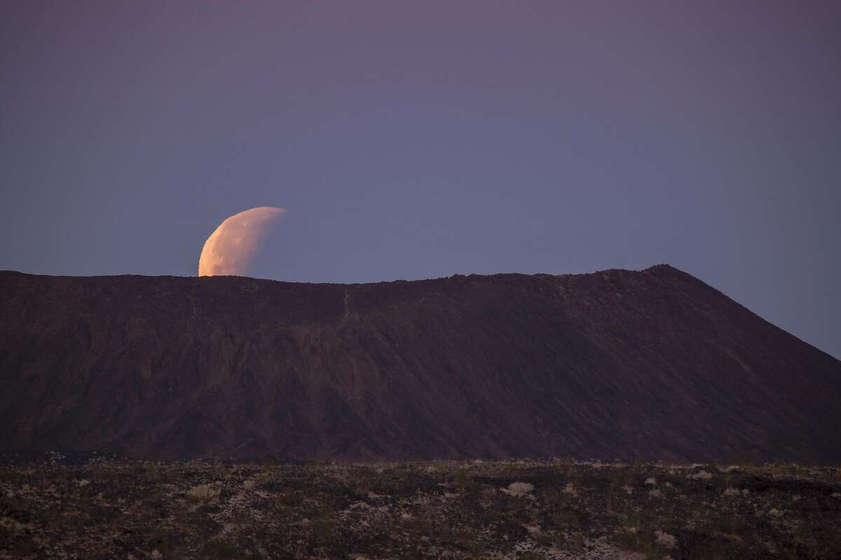 AMBOY, CA - JANUARY 31: A so-called 'super blue blood moon' sets behind Amboy Crater, a cinder cone volcano in the Mojave Desert, at the end of its total eclipse on January 31, 2018 near Amboy, California. The 'Super Blue Blood Moon' is a rare 'lunar trifecta' event in which the Moon is at its closest to the Earth, appearing slightly bigger and about 14 percent brighter than usual, and is simultaneously a 'blue moon', the second full moon in the same month, and in total lunar eclipse or 'blood moon'. Such a lunar event that hasn't been seen since 1866. (Photo by David McNew/Getty Images)