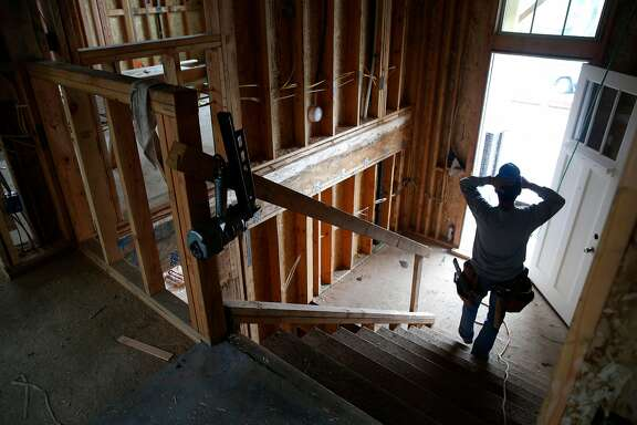 Eli Jacobo works inside a house under construction on Glenview Drive in the Crestmoor neighborhood of San Bruno, Calif. on Thursday, Jan. 18, 2018, one of the last to be rebuilt where 38 homes were destroyed by the deadly PG&E gas pipeline explosion seven years ago. Residents who lost their homes in the Wine Country Fires may face similar challenges when they begin to rebuild.