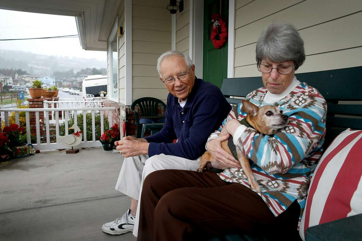 Charlie and Carolyn Gray sit with their dog JoJo on the front porch of their rebuilt home in the Crestmoor neighborhood of San Bruno, Calif. on Thursday, Jan. 18, 2018 where 38 homes were destroyed by the deadly PG&E gas pipeline explosion seven years ago. Residents who lost their homes in the Wine Country Fires may face similar challenges when they begin to rebuild.