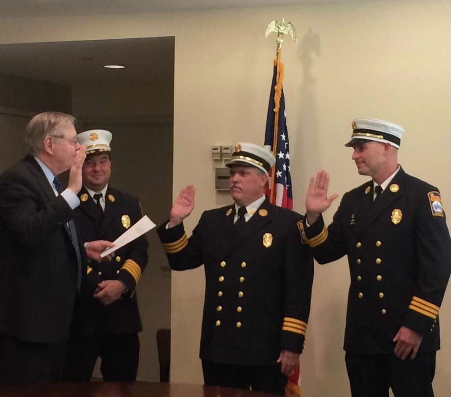 Mayor David Martin, left, stands next to Fire Chief Trevor Roach as he swears in deputy chiefs Thomas Gloersen, center, and Matthew Palmer Thursday at the government center. Photo: Libby Carlson / Contributed