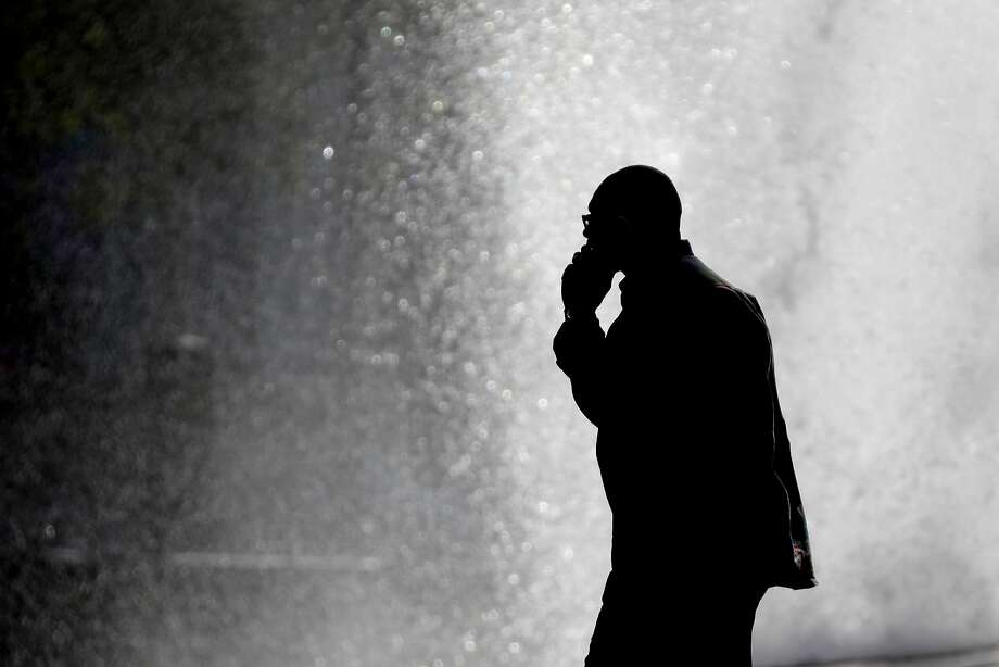 In this Thursday, Oct. 11, 2012 file photo, a pedestrian talking on a cellphone is silhouetted in front of a fountain at John F. Kennedy Plaza, also known as Love Park in Philadelphia. Released on Friday, Feb. 2, 2018, two government studies that bombarded rats and mice with cellphone radiation found a weak link to some heart tumors, but the research does not provide any clear answers about the safety of the devices that seem like extensions of our bodies. (AP Photo/Matt Rourke) Photo: Matt Rourke, Associated Press