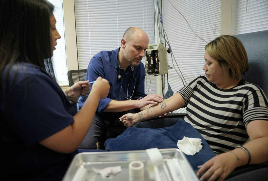 Dr. Carl J. Bonnett and medic Aleksandra Aguirre prepare National Guard Sgt. Blanca Torres for ketamine therapy. Torres have been visiting the San Antonio clinic to relieve her post-traumatic stress syndrome with IV does of the sedative. Photo: Darren Abate /San Antonio Express-News