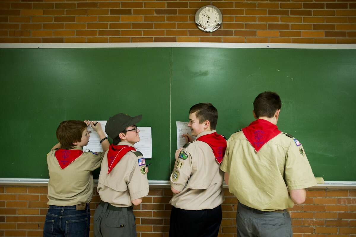 From left, Dakotah Fischer, 12, David Hasse, 14, Josh Whittington, 14, and Dylan Wedge, 14, laugh together while filling out a planning sheet for an upcoming trip during a meeting of Boy Scout Troop 761 on Friday, Jan. 23, 2018 at First United Methodist Church. (Katy Kildee/kkildee@mdn.net)