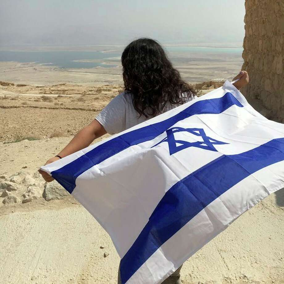Rachel Kessler, 17, holds the Jerusalem flag while looking out toward the open land in Israel. (Submitted Photo)