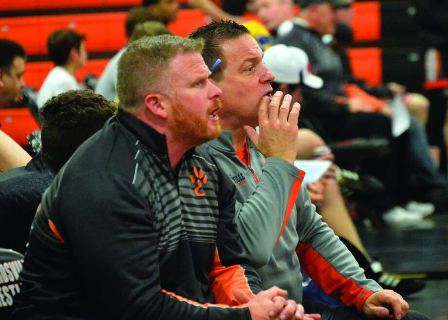 Edwardsville assistant coach Doug Heinz, front, and head coach Jon Wagner shout instructions during the heavyweight match of the Tigers' dual against Alton inside the Jon Davis Wrestling Center.
