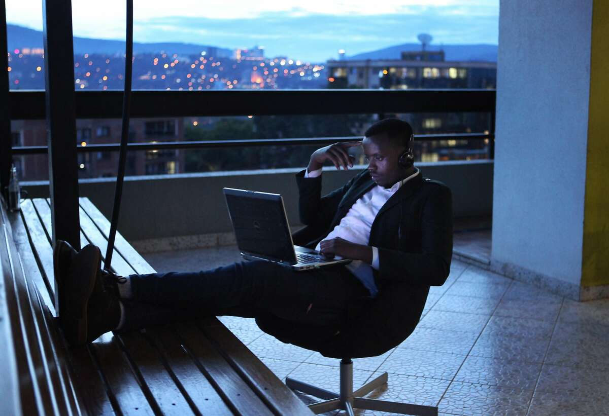 Entrepreneur and business owner Evariste Nayituriki, 27, puts his feet up as he works on kLab�s outdoor deck overlooking downtown Kigali as the sun sets on Nov. 15, 2017.