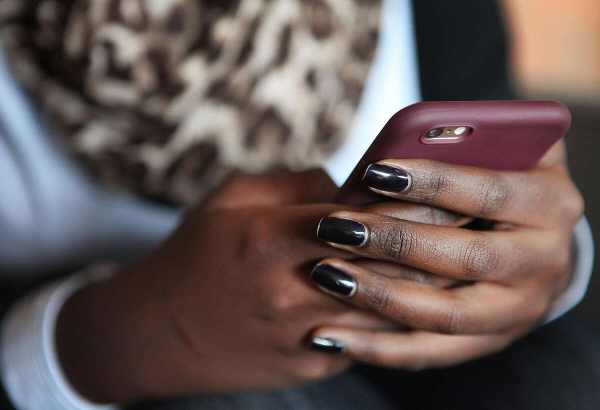 Yvette Mbabazi, 23, checks her iPhone at the Shokola Storytellers Caf� in Kigali during an interview with The Chronicle on Nov. 13, 2017. Mbabazi uses her phone to take photos and market brands, labels and fashion trends using social media. She is among a growing number of home-grown Internet celebrities in Kigali, who have thousands of social media followers and are adept at using technology to promote themselves or their businesses.