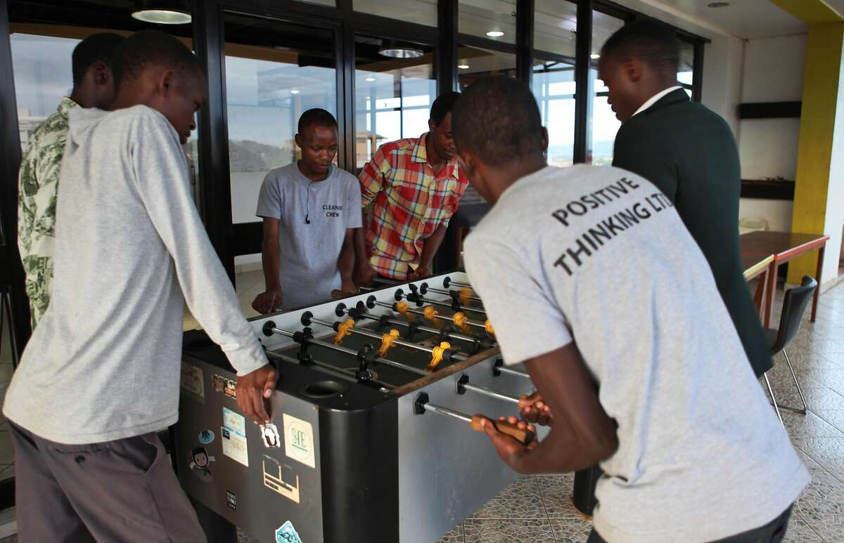 A group of entrepreneurs play a game of fooseball on the roof deck of kLab, a co-working space and tech hub in Kigali, on Nov. 15, 2017. The co-working space, like many in the United States, offers its members a place to work, high-speed Internet, a fooseball table, on-site caf� and more. It is among the biggest and most well-known tech lab in Rwanda.