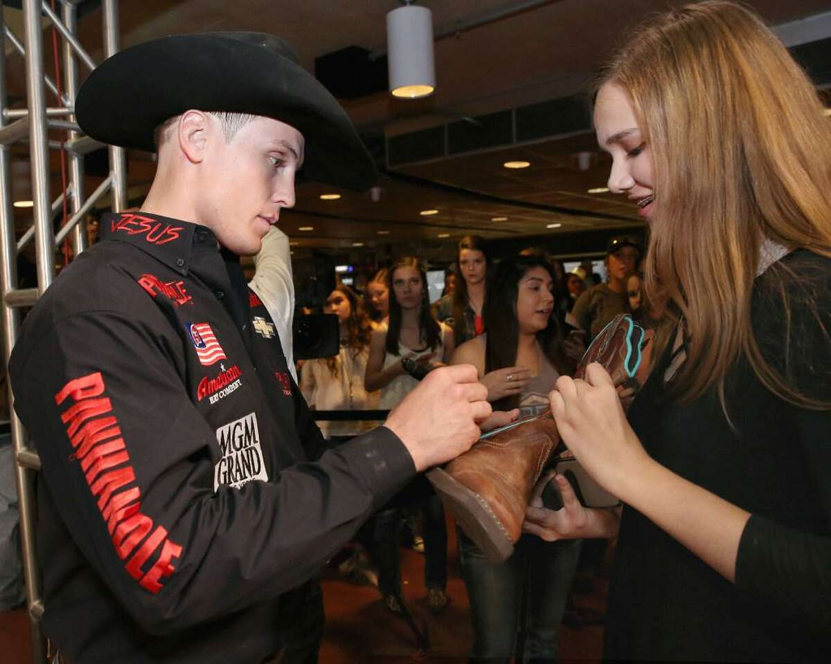 Tie-down roper Tuf Cooper signs Madison Sears' boot at the fan zone after his Houston Livestock Show and Rodeo Super Series 1 Round 2 competition at NRG Stadium March 8, 2017, in Houston.