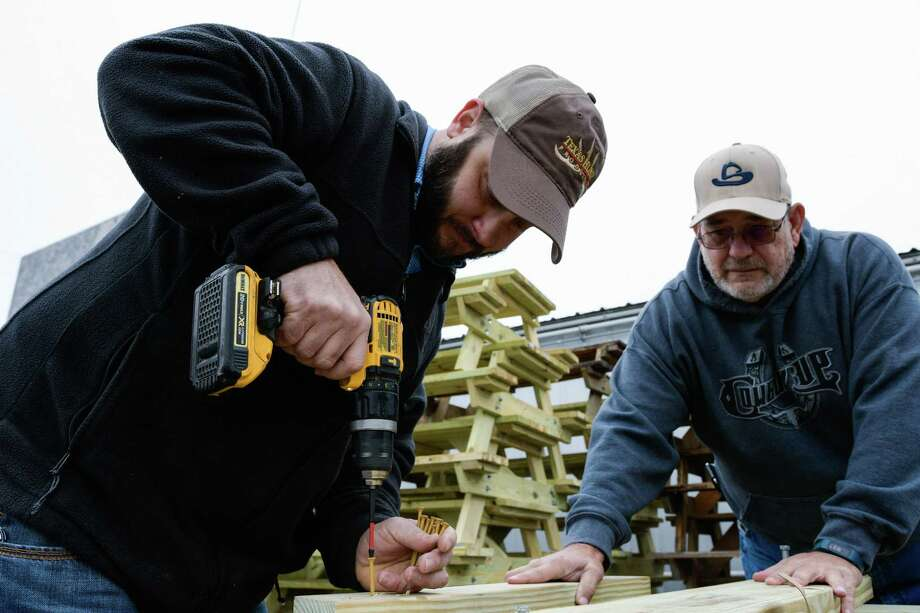 Volunteers Micheal Moore and Erine Simmions assemble picnic tables in preparation for the San Antonio Stock Show & Rodeo in January 2017. Photo: Charlie Blalock / For The Express News
