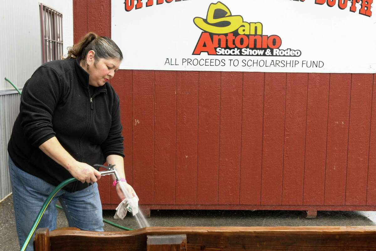 Volunteer Betty Cruz washes off benchs in preparation for the San Antonio Stock Show & Rodeo in January 2017.