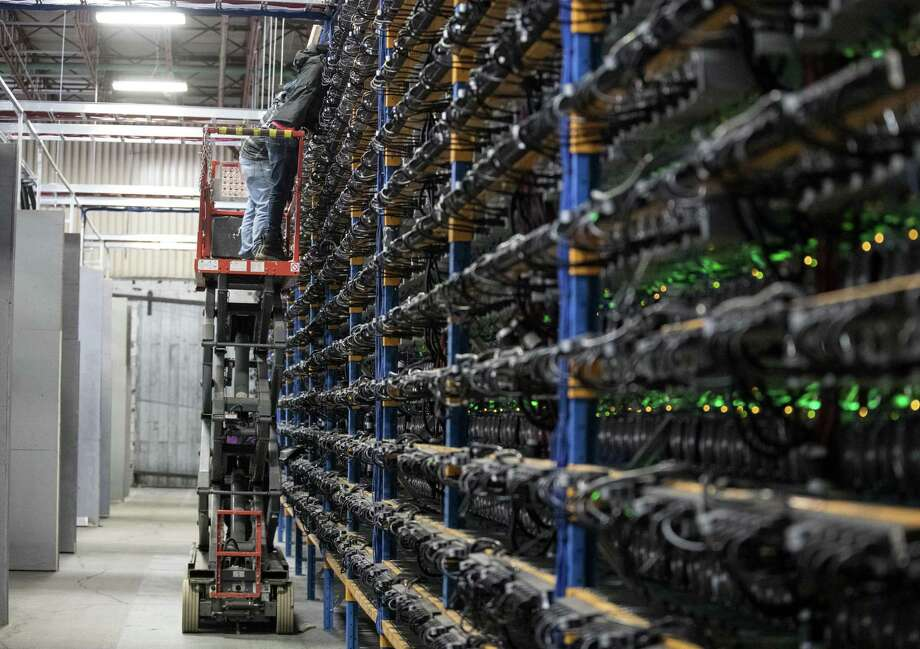 An employee inspects mining machines at the Bitfarms cryptocurrency farming facility in Farnham, Quebec, Canada, on Wednesday, Jan. 24, 2018. Photo: Christinne Muschi /Bloomberg / © 2018 Bloomberg Finance LP