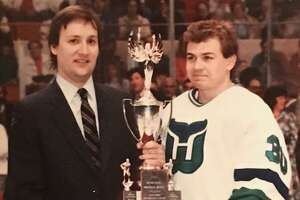 Columnist Jeff Jacobs presents Hartford Whalers goalie Peter Sidorkiewicz with an award in 1989.