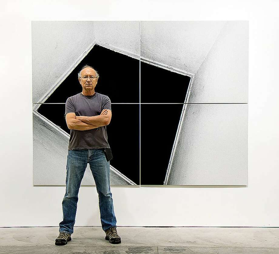 "The late Oakland photographer Steve Kahn stands in front of one of his mural-size works at S.F.'s Casemore Kirkeby, which is exhibiting his collection titled ""Corridors"" through May 26. Photo: Casemore Kirkeby"