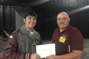 Joshua Pink, left, a senior at San Antonio Christian School, suggested donating proceeds from his class's annual barbecue to First Baptist Church of Sutherland Springs. The pastor, Frank Pomeroy, accepted the gift Friday and spoke to the students.