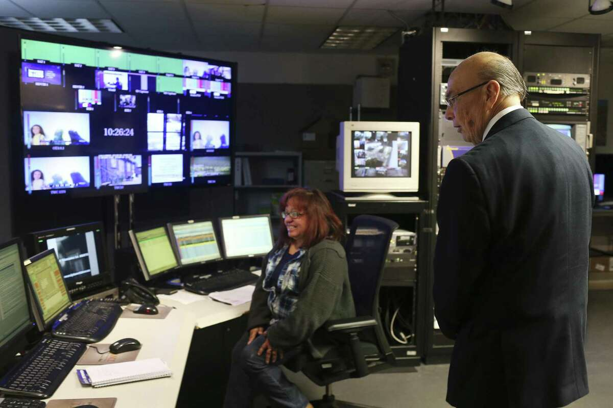KLRN CEO Arthur Rojas Emerson visits the control room while giving a tour of their studios on Broadway Street, Thursday, Feb. 1, 2018. On the controls is Mary Salazar.