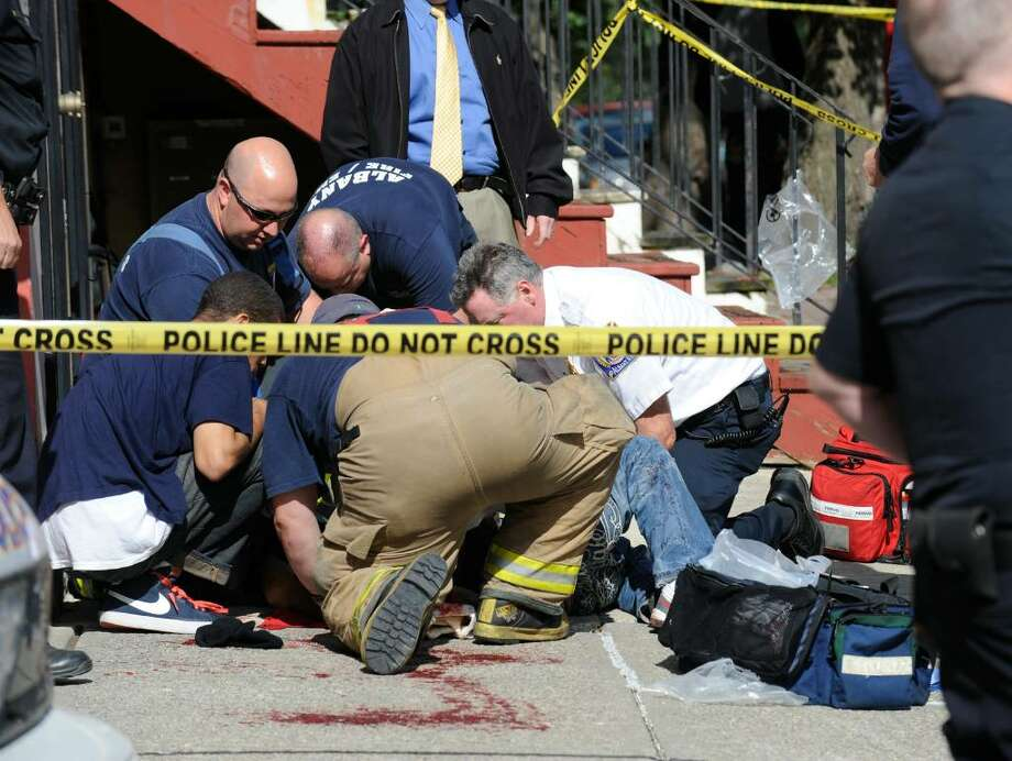 Paramedics tend to a  victim at the intersection of Grand Street and Myrtle Street in Albany today.    (Skip Dickstein / Times Union) Photo: SKIP DICKSTEIN / 2008