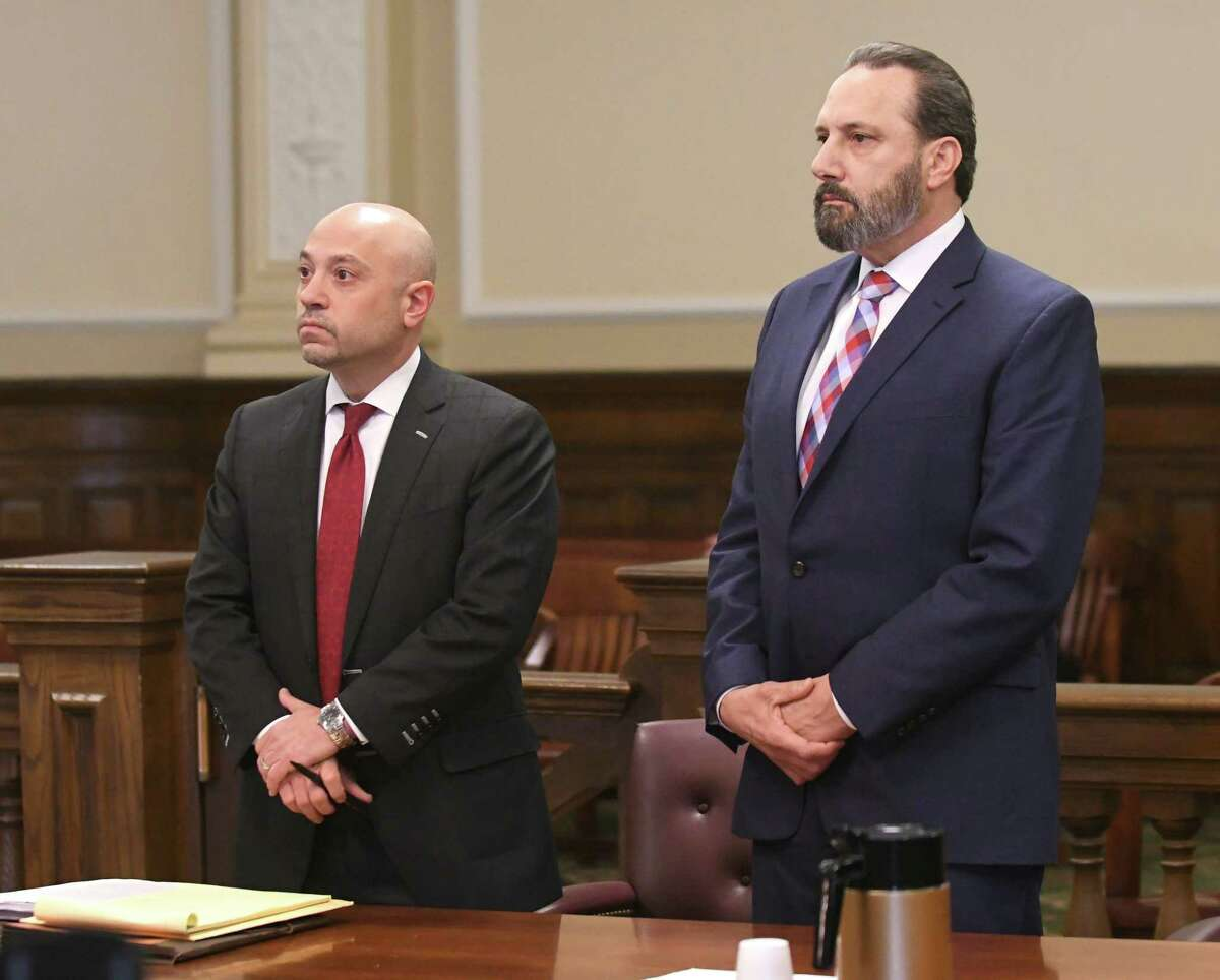 Defense attorney Andrew Safranko left, stands with his client, detective John Comitale Jr., as Albany County Court Judge Peter Lynch opens a sealed indictment at the Rensselaer County Court House on Friday, Feb. 2, 2018, in Troy, N.Y. (Lori Van Buren/Times Union)