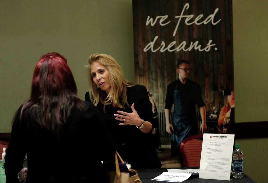 In this Tuesday, Jan. 30, 2018, photo, Grace Ochoa, of Performance Food Service, right, talks with a job applicant at a JobNewsUSA job fair in Miami Lakes, Fla. On Friday, Feb. 2, the U.S. government issues the January jobs report. (AP Photo/Lynne Sladky) Photo: Lynne Sladky, STF / Copyright 2018 The Associated Press. All rights reserved.