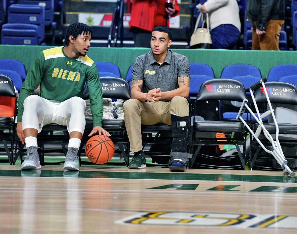 Benched because of a stress injury to his left heel bone, Siena freshman point guard Roman Penn, right, is consoled by team mate Ahsante Shivers before their MAAC game against Manhattan at the Times Union Center Friday Feb. 2, 2018 in Albany, NY. (John Carl D'Annibale/Times Union)