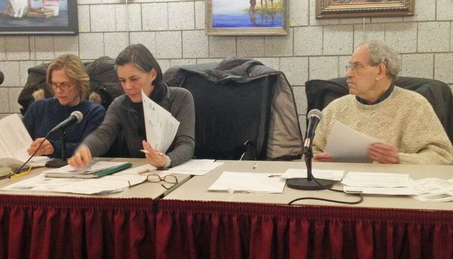 Commission members from left Carolyn Free, Chantal Foster and chairman Bruce Tyler review the Elmcrest proposal before voting to approve it Thursday night in Portland. Photo: Jeff Mill / Hearst Connecticut Media