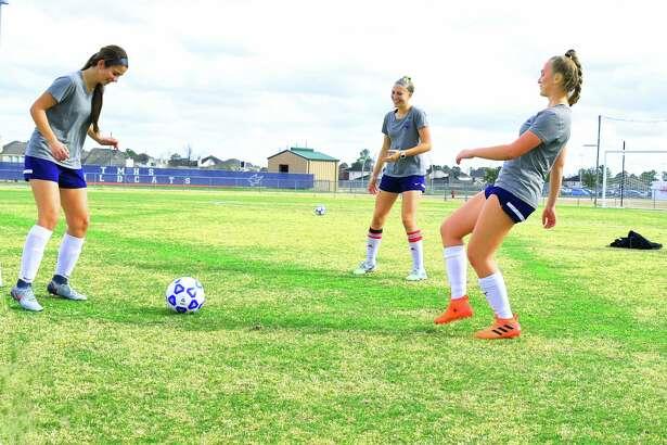 Tomball Memorial players Sarah Guilstorf, Lorela Stramrood, Savannah Keziah work on drills during practice.