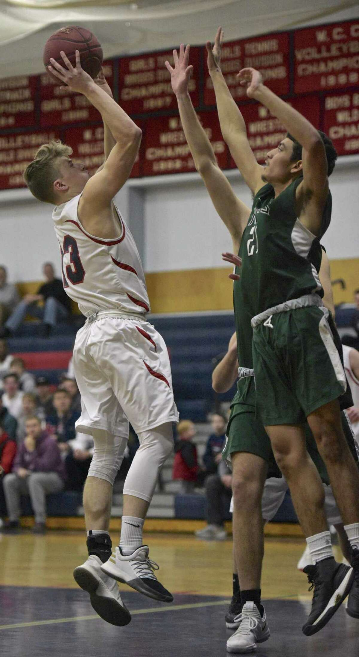 New Fairfield's Sean Jamieson (13) takes a shot over New Milford's Josian Morales (21) in the boys basketball game between New Milford and New Fairfield high schools on Friday night, February 2, 2018, at New Fairfield High School, in New Fairfield, Conn.