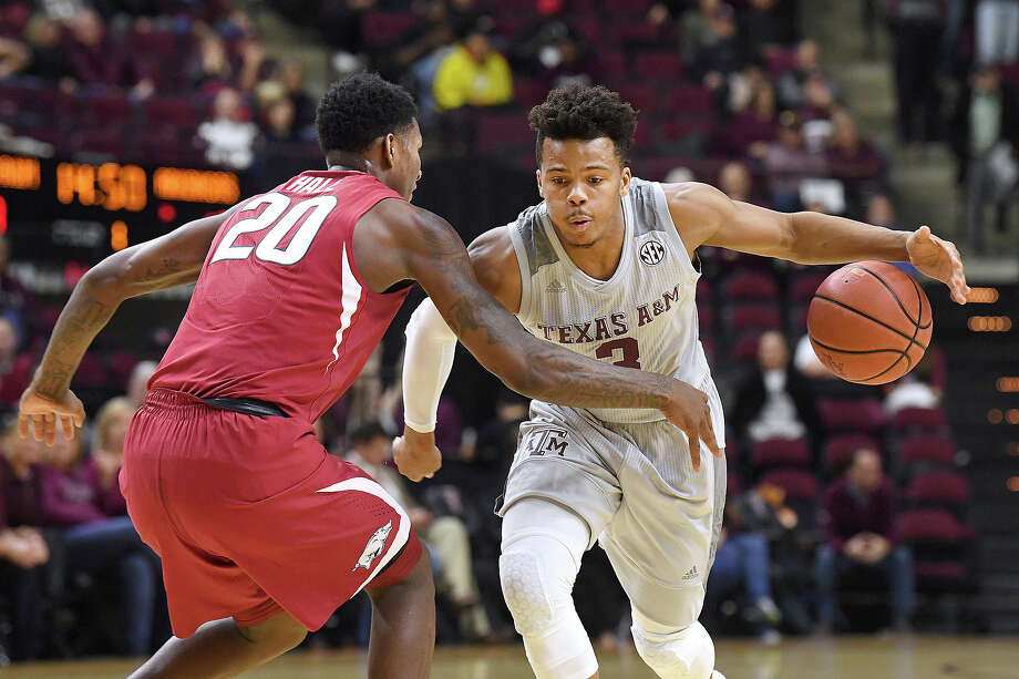 Texas A&M's Admon Gilder (3) tries to keep the ball away from Arkansas' Darious Hall (20) during the first half of an NCAA college basketball game Tuesday, Jan. 30, 2018, in College Station, Texas. (Laura McKenzie/College Station Eagle via AP) Photo: Laura McKenzie, Associated Press / College Station Eagle