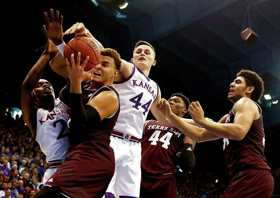 LAWRENCE, KS - JANUARY 27:  DJ Hogg #1 of the Texas A&M Aggies tries to control the ball as Lagerald Vick #2 and Mitch Lightfoot #44 of the Kansas Jayhawks defend during the game at Allen Fieldhouse on January 27, 2018 in Lawrence, Kansas. Photo: Jamie Squire, Getty Images / 2018 Getty Images