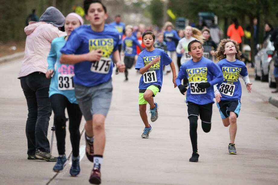 Race participants approach the finish line during Kids Running for Kids on Saturday, Feb. 3, 2018, at Town Green Park in The Woodlands. Photo: Michael Minasi, Staff Photographer / © 2017 Houston Chronicle