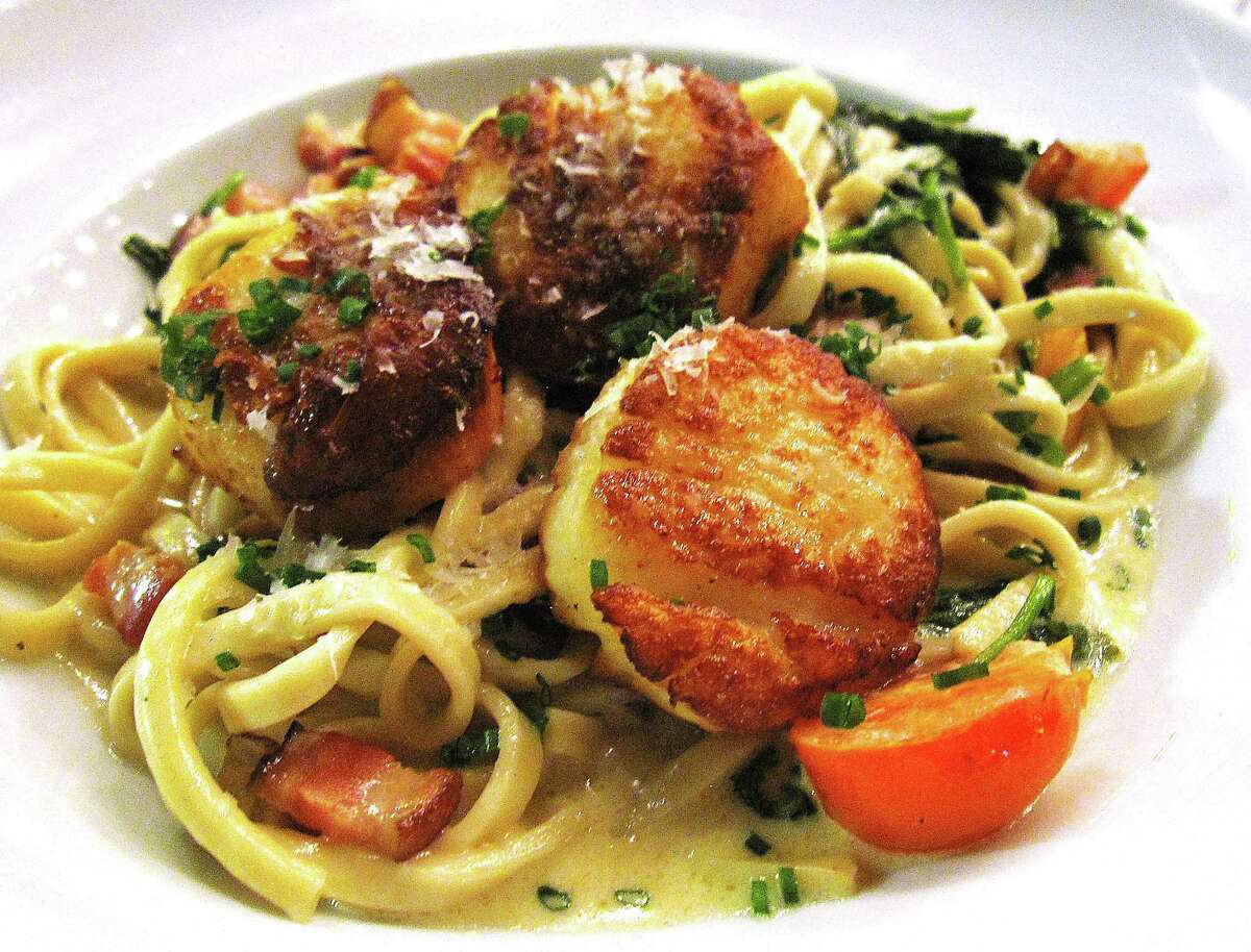 Seared scallops with linguine, spinach, lardons, cherry tomatoes and Brussels sprouts from Il Sogno.