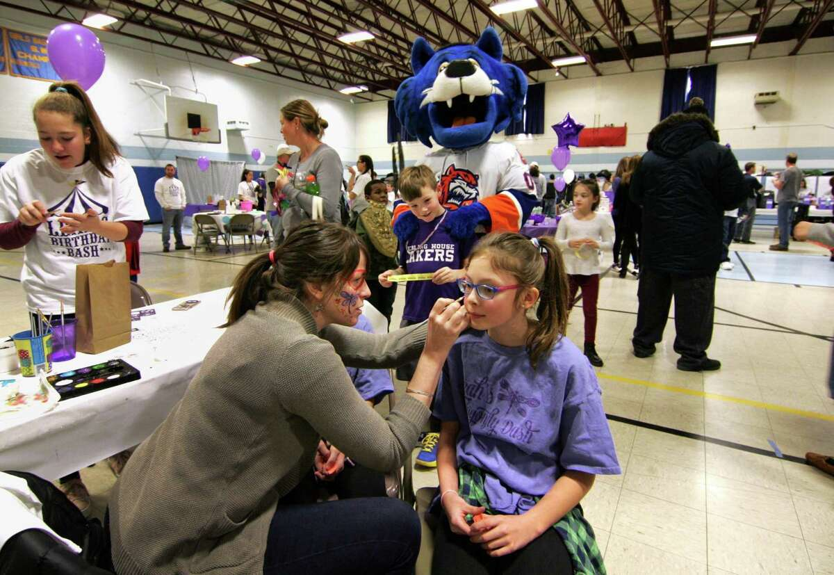 Madison Gallant, 11, gets her face painted during the 3rd Annual Leah Rondon Birthday Bash benefit indoor carnival to honor the life of Leah Rondon at Kolbe Cathedral in Bridgeport, Conn., on Saturday Feb. 3, 2018. The carnival's proceeds benefit the Leah Rondon Memorial Scholarship Fund.