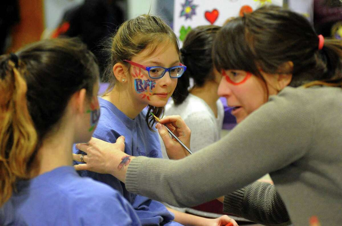 Madison Gallant, 11, center, and Sophie DeLise, 9, get their faces painted during the 3rd Annual Leah Rondon Birthday Bash benefit indoor carnival to honor the life of Leah Rondon at Kolbe Cathedral in Bridgeport, Conn., on Saturday Feb. 3, 2018. The carnival's proceeds benefit the Leah Rondon Memorial Scholarship Fund.