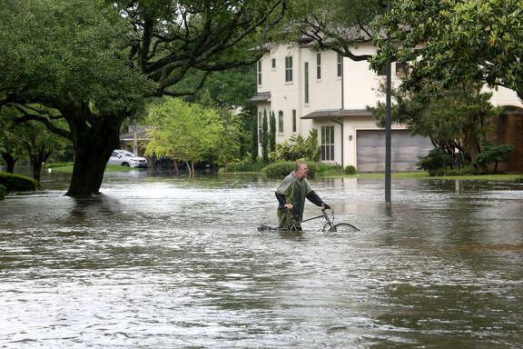 A Houston man makes his way along an inundated portion of Chimney Rock after Brays Bayou flooded the Meyerland area in April 2016.