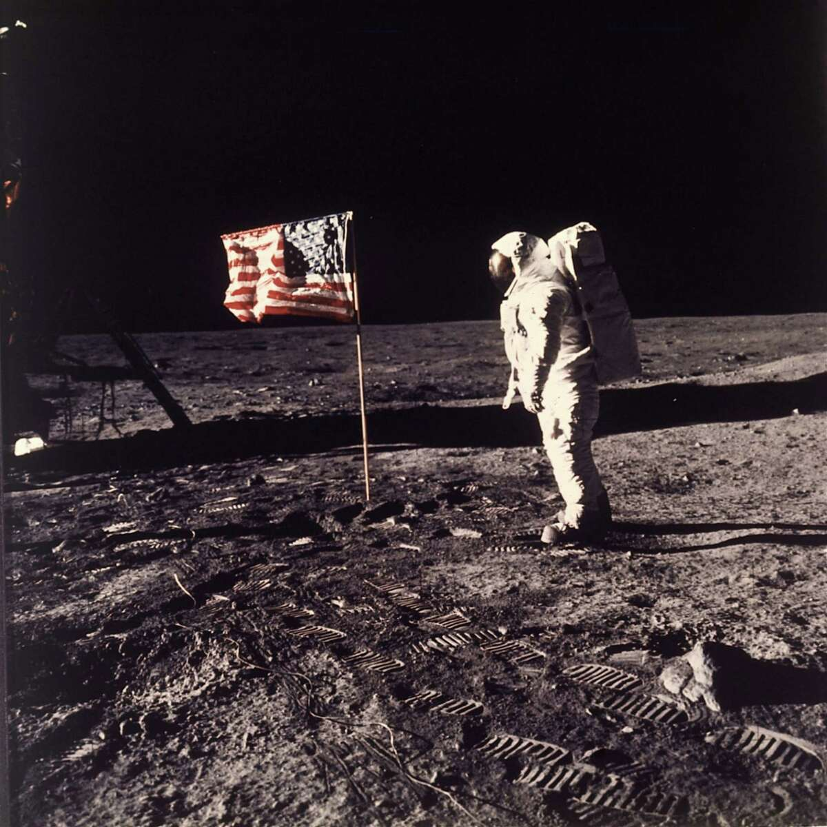 """Astronaut Edwin E. """"Buzz"""" Aldrin Jr. is captured in time beside the U.S. flag planted on the moon during the Apollo 11 mission on July 20, 1969."""